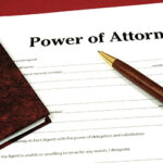 Power of attorney document with pen and legal book.